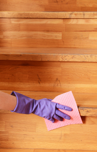 Female hand in rubber glove cleaning staircase