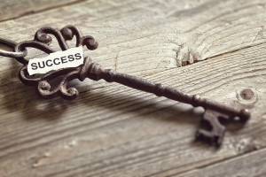 Antique key with word success written on paper resting on wooden surface concept for aspirations and success